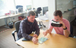 Doug Appleton (left) and Matt Mills demonstrate their headset's eye-tracking capabilities at SyncThink as part of a ...