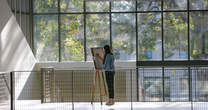 A student works on a painting in the Creative Art and Design Building