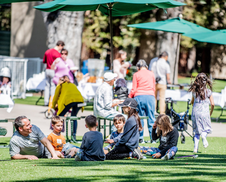 Adults and children relax on the Upper School Quad